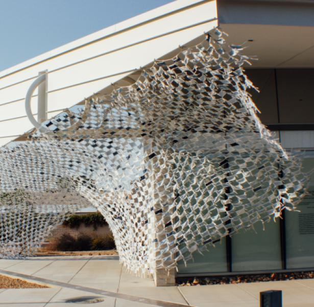 Installation view of Wave by artists Debra Everett and Ronna Nemitz. Over 2000 handmade masks blow in the wind on the exterior of MCC Art Gallery.