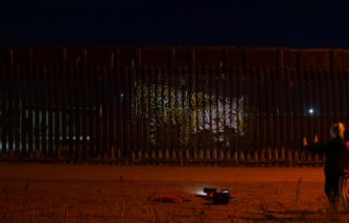 "Strohacker's projection ""Unfragmenting/Des Fragmentando"" on the US Mexico Border Fence"