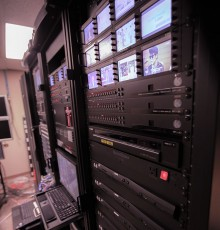 Rack of headend technology streaming encoders and preview monitor displays.