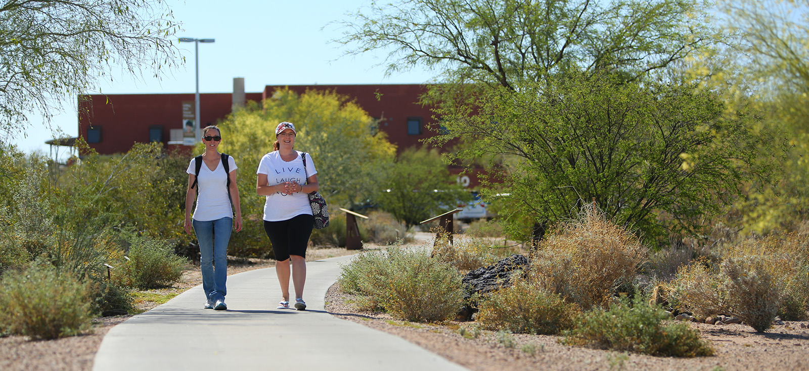 Two students walking across the MCC Red Mountain Campus