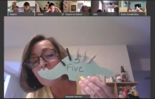 Rochelle Ramirez-Clark shows a picture of a dinosaur cut out with the number 5 printed on it. The dinosaur has five clothespins attached as spikes on it's back.
