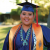 Smiling indigenous female student in blue graduation cap and gown with honor cords and turquoise necklace.