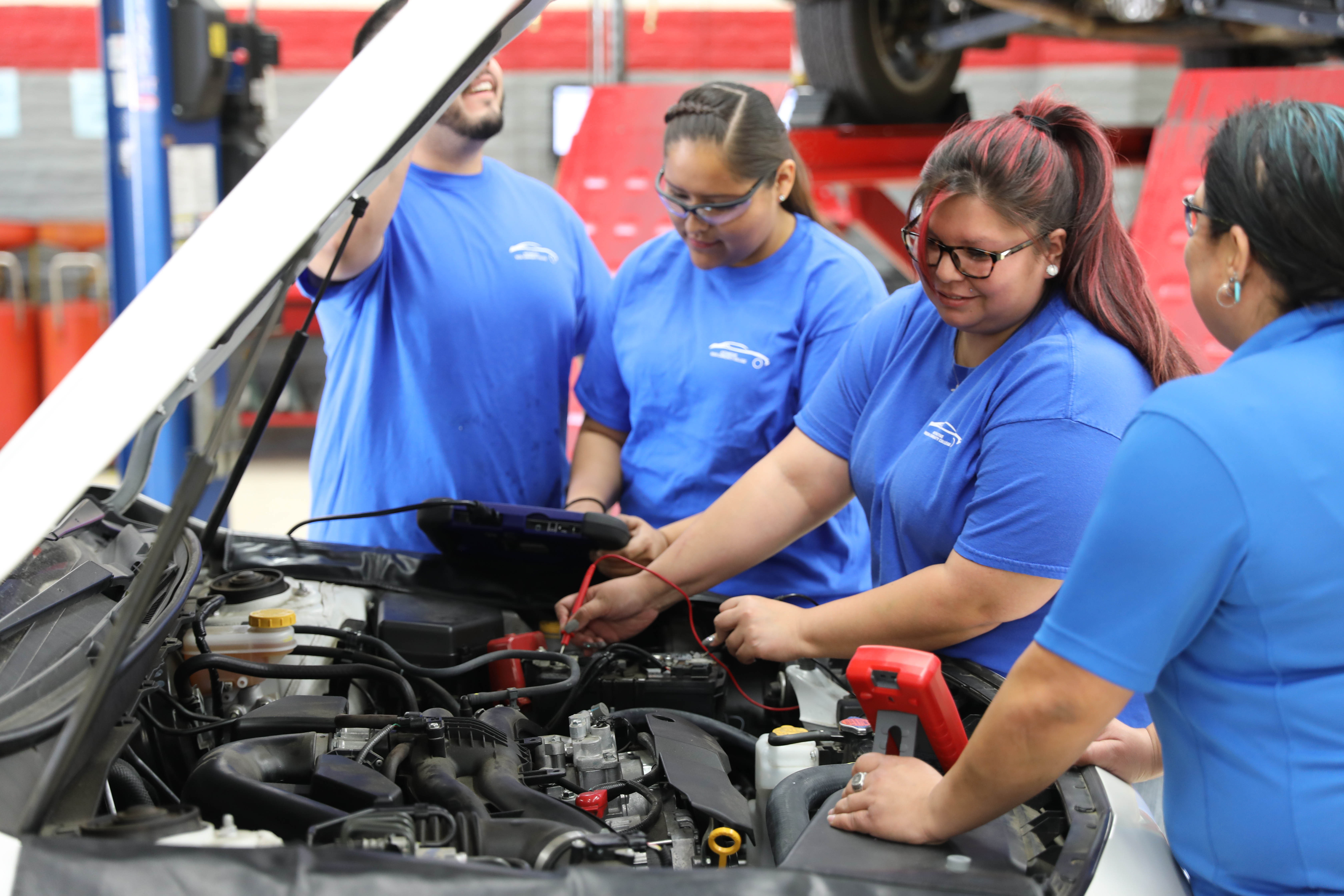 Students using diagnostic tools on Subaru Outback engine